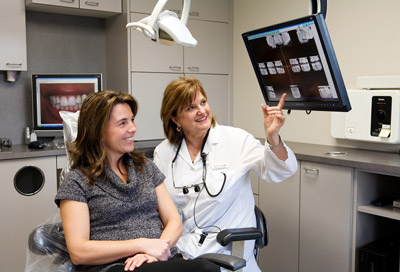 Woman looking at x-rays with her dentist at Spektor Dental in Bellevue, WA